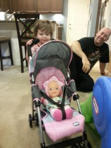 Pushing her doll in a stroller