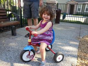 Riding her tricycle